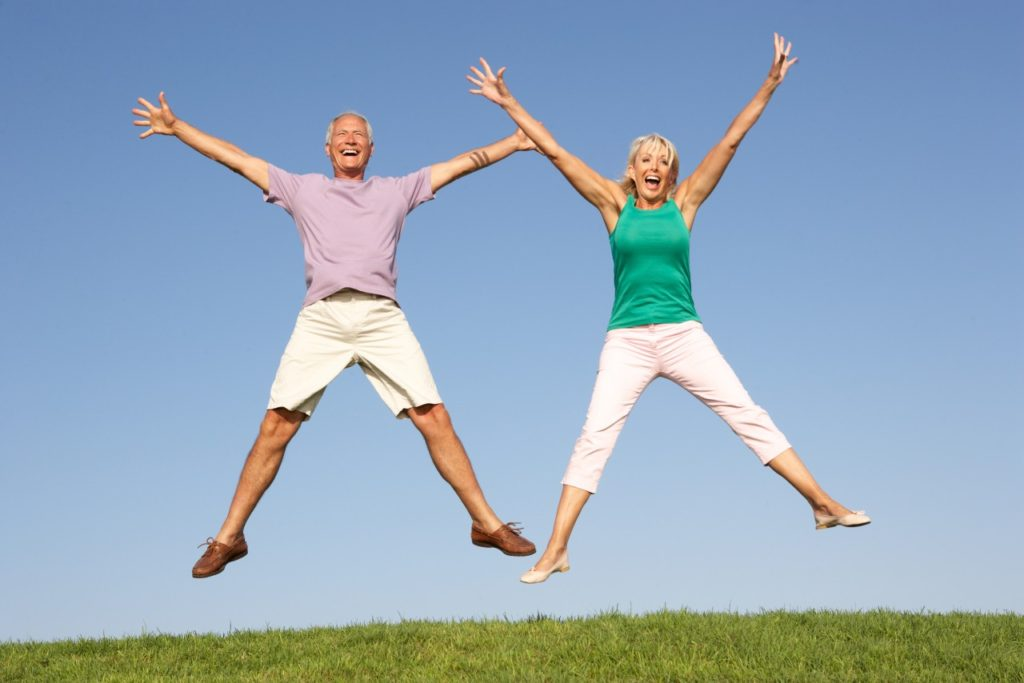 Senior couple jumping in air